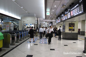 A scene of the station showing people near the ticket barrier gates.
