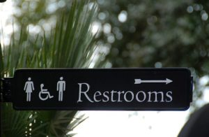 Directional sign to toilets in an outdoor area.