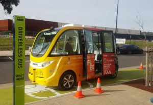 A yellow automated vehicle is parked by the footpath.
