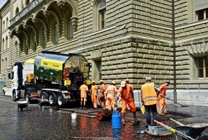 Road workers in hi-vis vests are laying bitument