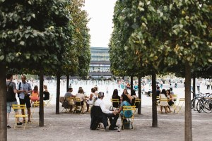 Open area with trees and people seated at tables in an outdoor cafe.