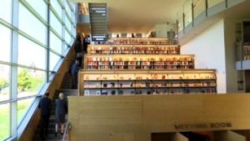A long flight of stairs on the left looks out over Manhattan with rows of books tiered up on the right hand side. They are only accessible via the stairs.