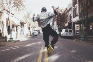A young man is in the middle of a residential street. He looks like he is jumping or dancing.