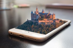 A smartphone is laying flat on the table and rising out of it is a three d castile building.