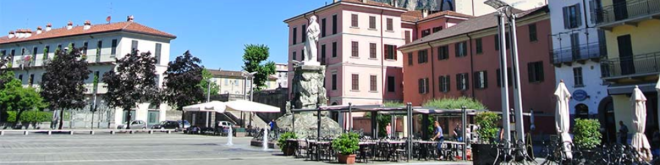 Lecco Square, Italy showing four storey heritage buildings and a statue.