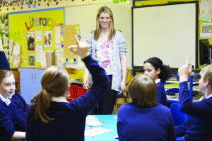 A female teacher stands smiling in front of a class of young students in school uniform. One has her arm raised as if to ask or answer a question.