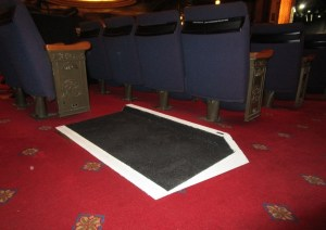 The portable ramp is placed within the auditorium at the end of an aisle.