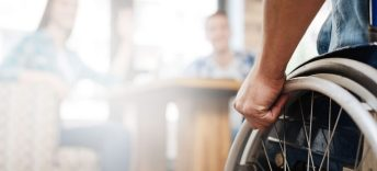 A wheelchair user enters the frame on the left hand side. The background is a blurred out cafe setting.