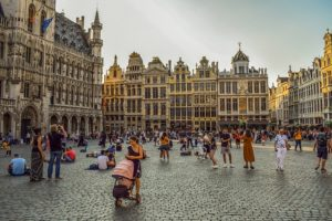 A city square in Belgium showing heritage architecture. People are milling about in the square.