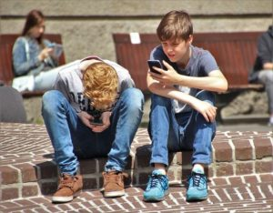 Two male adolescents sit on the kerb looking at the phones.