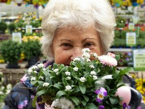 An older woman with white hair holds a bouquet of flowers to her face. Her eyes indicate she is smiling.