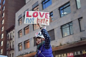 A girl holds up a sign that says, Love not Hate. She appears to be sitting on the shoulders of someone in a public street march.