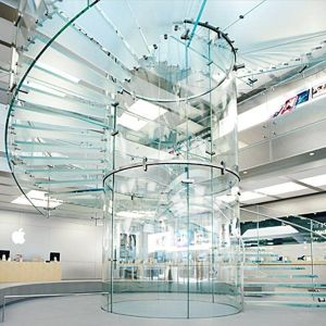 A curved open tread glass stairway in a New York retail store. It has little contrast with its surroundings.