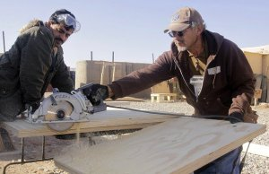 Two men are working on a construction site. One is holding a circular saw which has just cut through a large timber board.