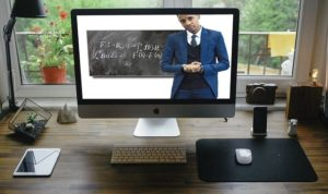 A computer screen shows a man in a blue jacket standing in front of a blackboard.