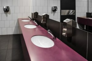 a row of public toilet handbasins sit in front of a large mirror. There are sensor taps and soap dispensers.
