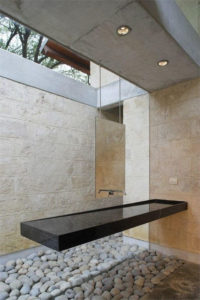 A long black sink shaped like a shelf hangs longways from the wall. The backwall is full length window and it is difficult to see the tap. It looks very modern.