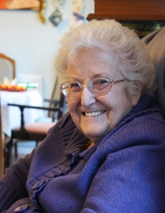 An older woman sits in an armchair. She is wearing a purple knitted jacket and is smiling into the camera.