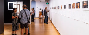 An display space at QUT Art Museum. People are looking at small pictures hanging on a white wall.