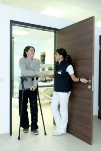 A young man with crutches walks through a door held open by a clinician.