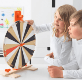 A boy and girl look at a children's wood spinning wheel.