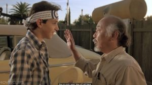 A still from the movie, The karate Kid, where Mr Miyagi teaches Daniel the 'wax-on, wax-off' routine.