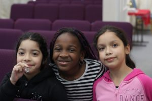Three girls of colour smile at the camera. They are in a room with rows of chairs.