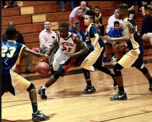 Black boys in action on the basketball court.