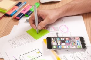 A hand holding a coloured pen is poised over a green post it note. There are drawings on the table and a smartphone. It indicates UX design.