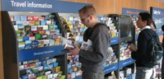 two people stand in front of racks of tourism brochures.
