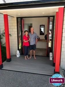 Max and Tricia stand at their doorway which reflects their love of Japanese design.