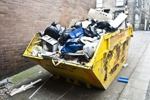 A yellow skip bin is overflowing with rubbish.
