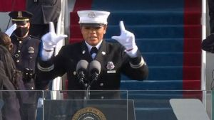 Firefighter Andrea Hall in full dress uniform and white gloves signs during the inauguration of Biden and Harris.