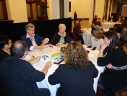 Table Topics group at a previous conference. Men and women are sitting at a round table have a discussion.