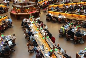 Aerial view of rows of desks in a public library and people sitting at desks.
