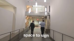 Two people walk down a ramp signing to each other.