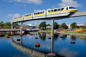 Disney monorail travelling on a raised rail over water.