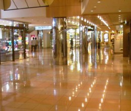 A shopping mall with a shiny floor reflecting rows of lights from the ceiling. It looks very confusing.