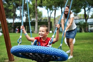 A small boy sits in a basket swing. He is smiling as a woman is pushing the swing.