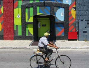 An older man rides his bicycle along a street. In the background is a brightly coloured mural.
