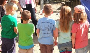 Five small children stand in a line with their backs facing the camera. Kindergartens inclusive spaces for all children.