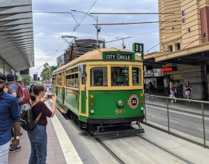 People waiting at a Melbourne tram stop. The tram is approaching. Transport and Health Guidebook.