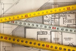 A building plan with two yellow and one white tape measure across it.