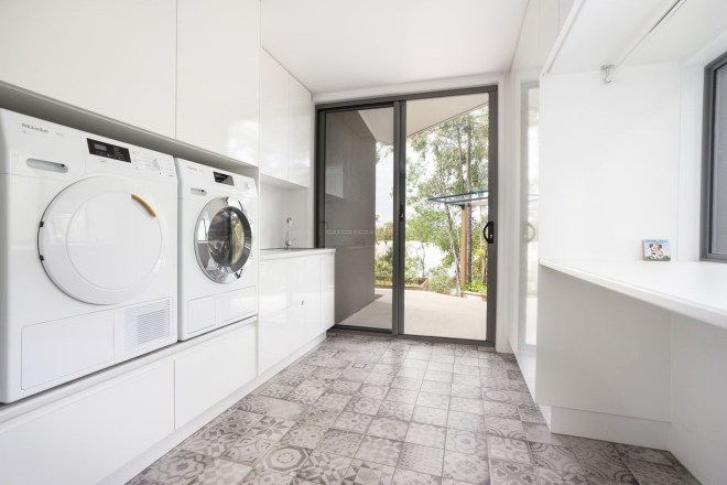 Laundry with white fittings. Washer and Dryer raised up.