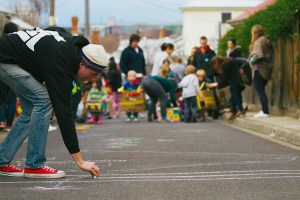 A man is drawing chalk lines on the roadway. In the background children are gathered. 1000 Play Streets Toolkit.