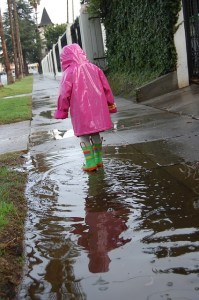 A child in a pink raincoat stands in a puddle in the footpath after the rain. Inclusive streets are safe, obvious and step-free.