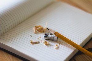 An empty page in a notebook with a pencil and sharpener. Doing plain language is a process