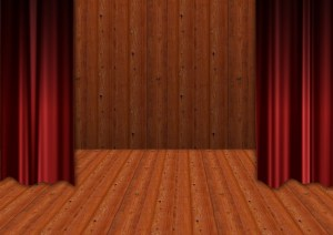 An empty stage flanked by dark red curtains. UX design without users.