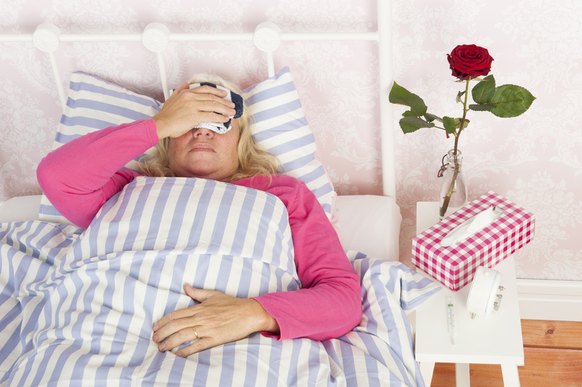 Woman With Migraine Lying In Bed