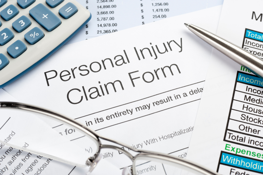 Personal Injury Claim Form With Pen, Calculator